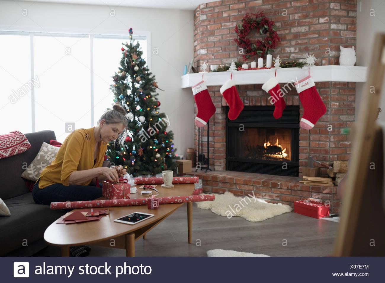Reife Frau Verpackung Weihnachtsgeschenke in der Nähe der Kamin im ...