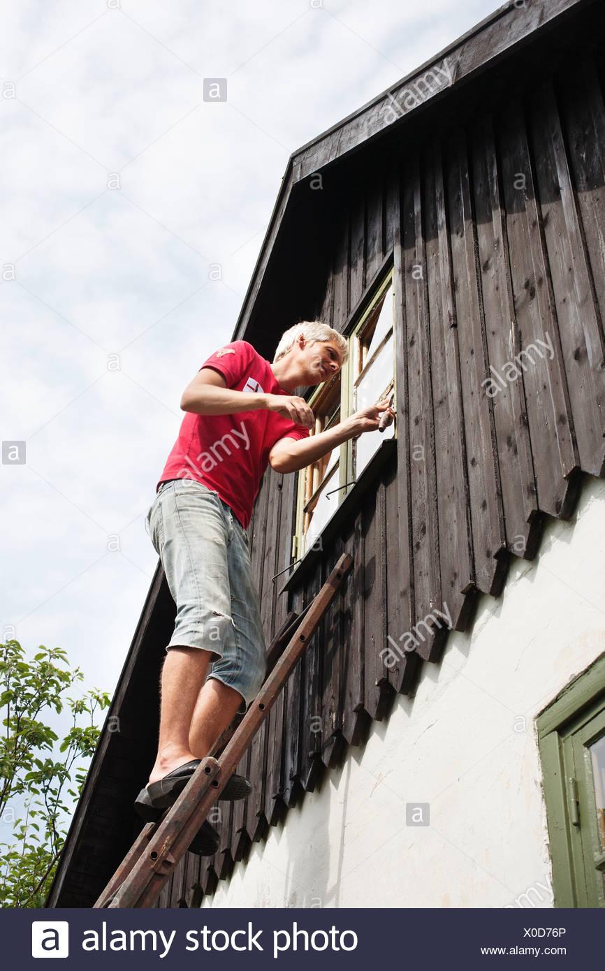 Mann auf Leiter Reparatur Fenster Stockfoto, Bild: 275656942 - Alamy