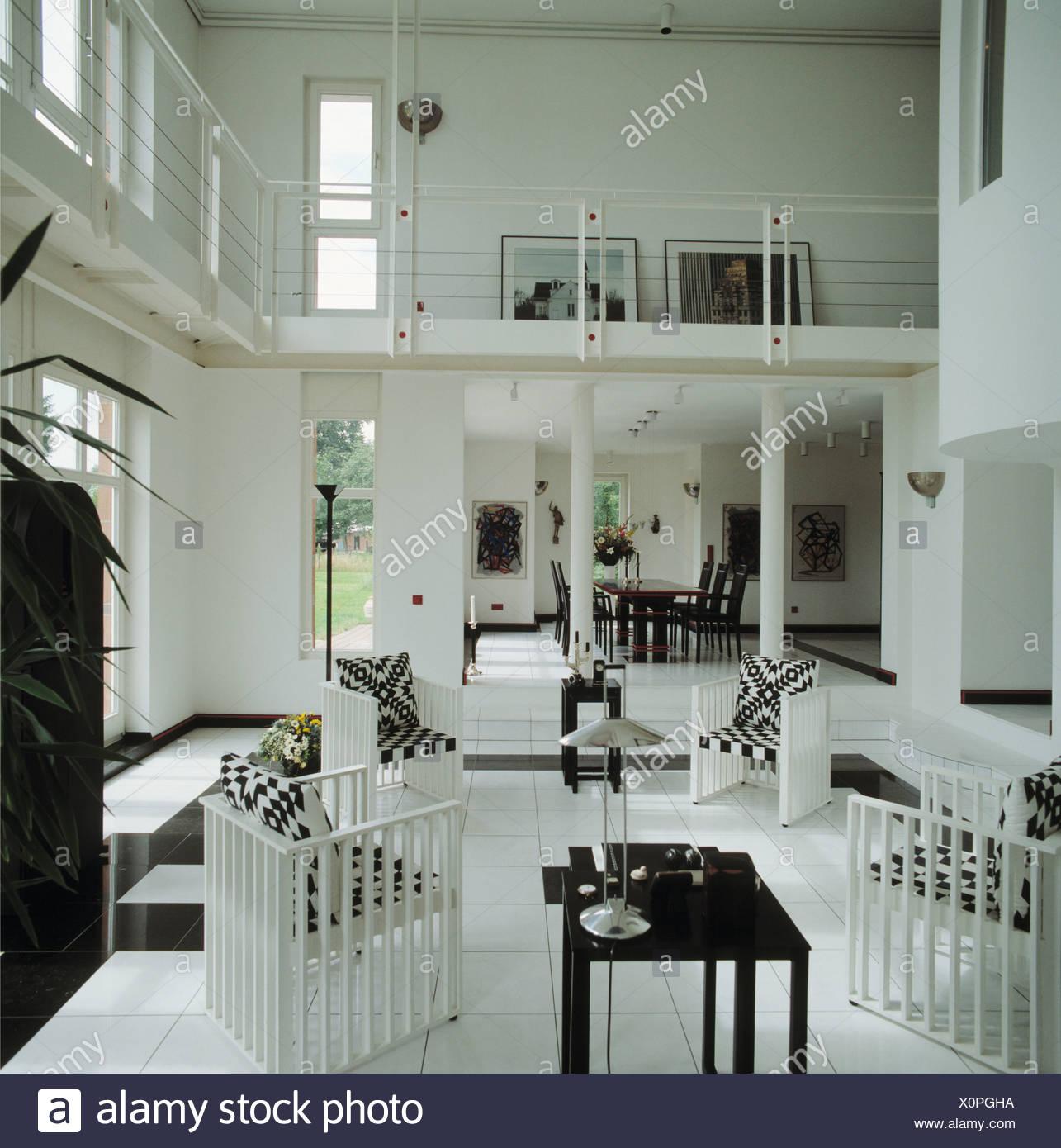 Schwarz / Weiß Kissen Auf Weißen Stühlen In Doppelter Höhe Moderne Offene  Wohnzimmer Mit Galerie Und Weißen Fliesenboden