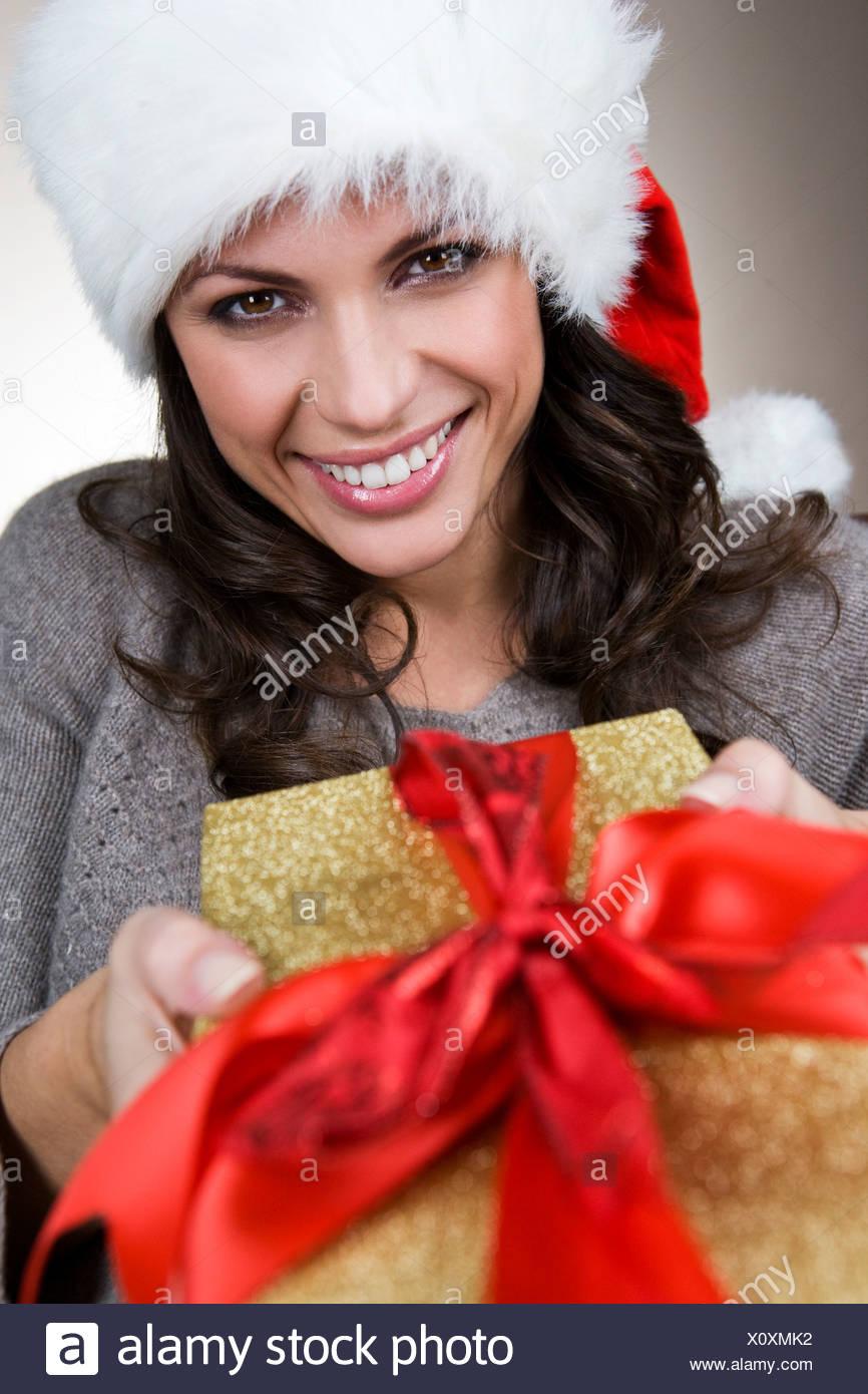 Eine junge Frau trägt eine Weihnachtsmütze hält ein ...