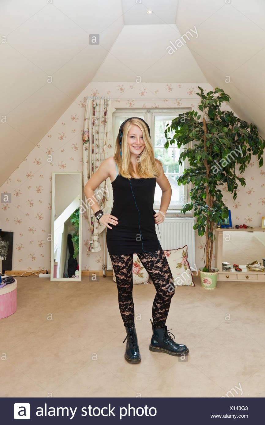 Ein Punk Teenager Mädchen In Einem Konservativ Dekorierten Schlafzimmer  Stehen