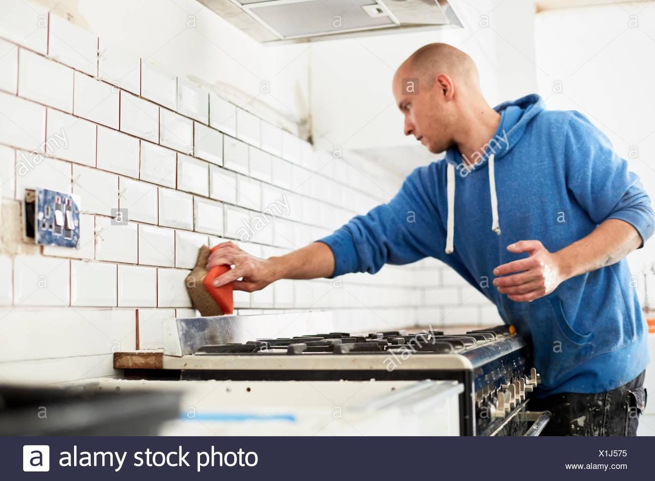 Ein Mann in eine neue Küche, ein Fliesenleger Fliesen an der Wand ...