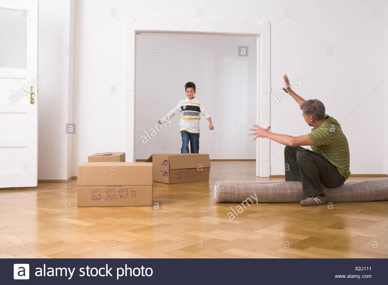 Vater sitzt auf gerollten Teppich Sohn spielt mit Boxen als sie ...