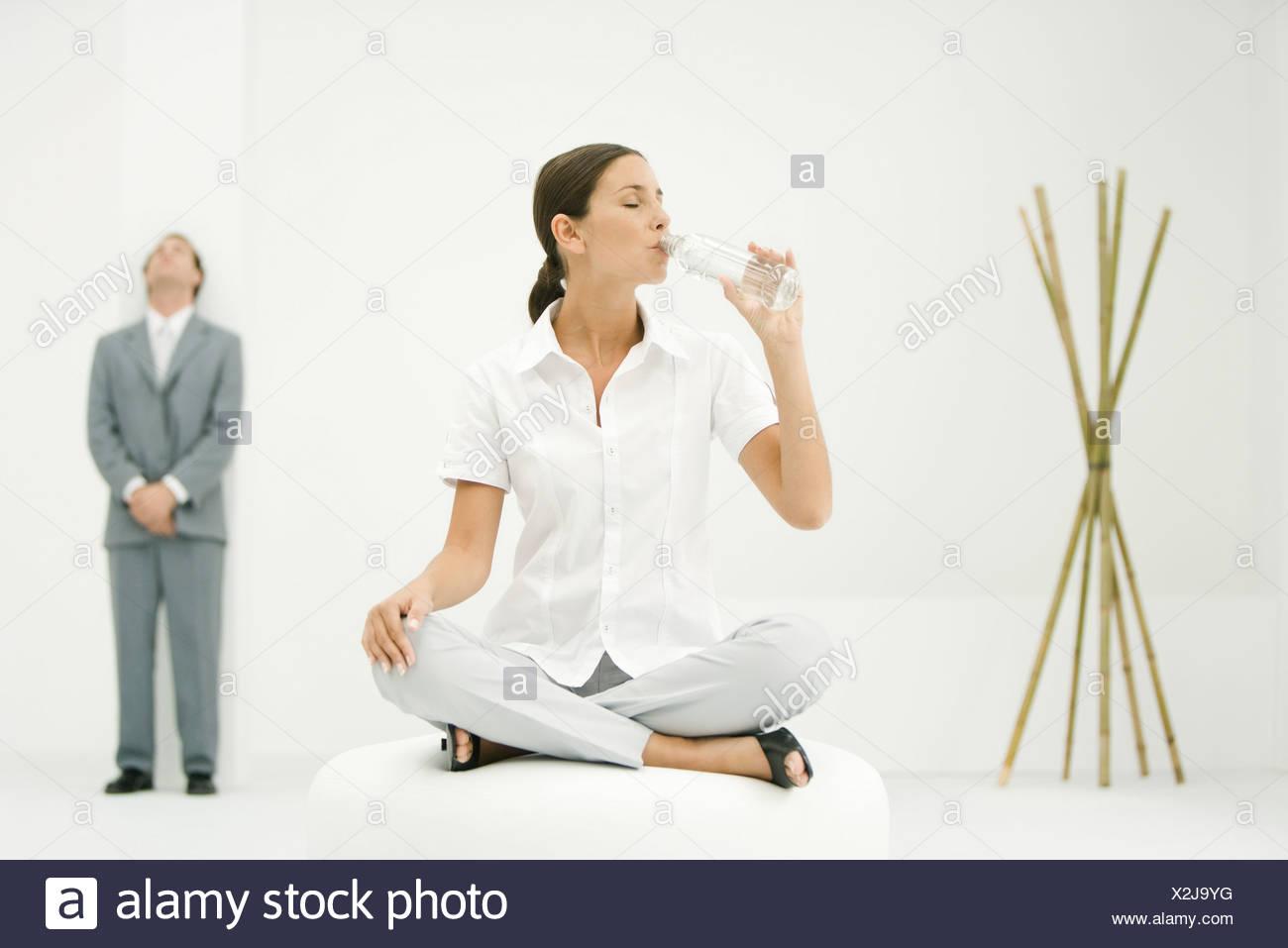 Berufstatige Frau Sitzen Auf Ottomane Trinken Aus Der Flasche