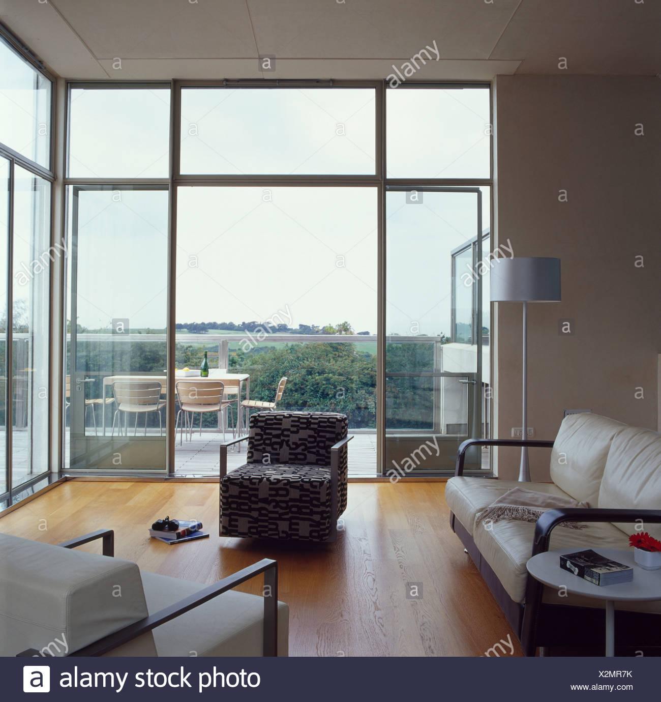 Creme Ledersofa und gemusterten Sessel in großen modernen Wohnzimmer ...
