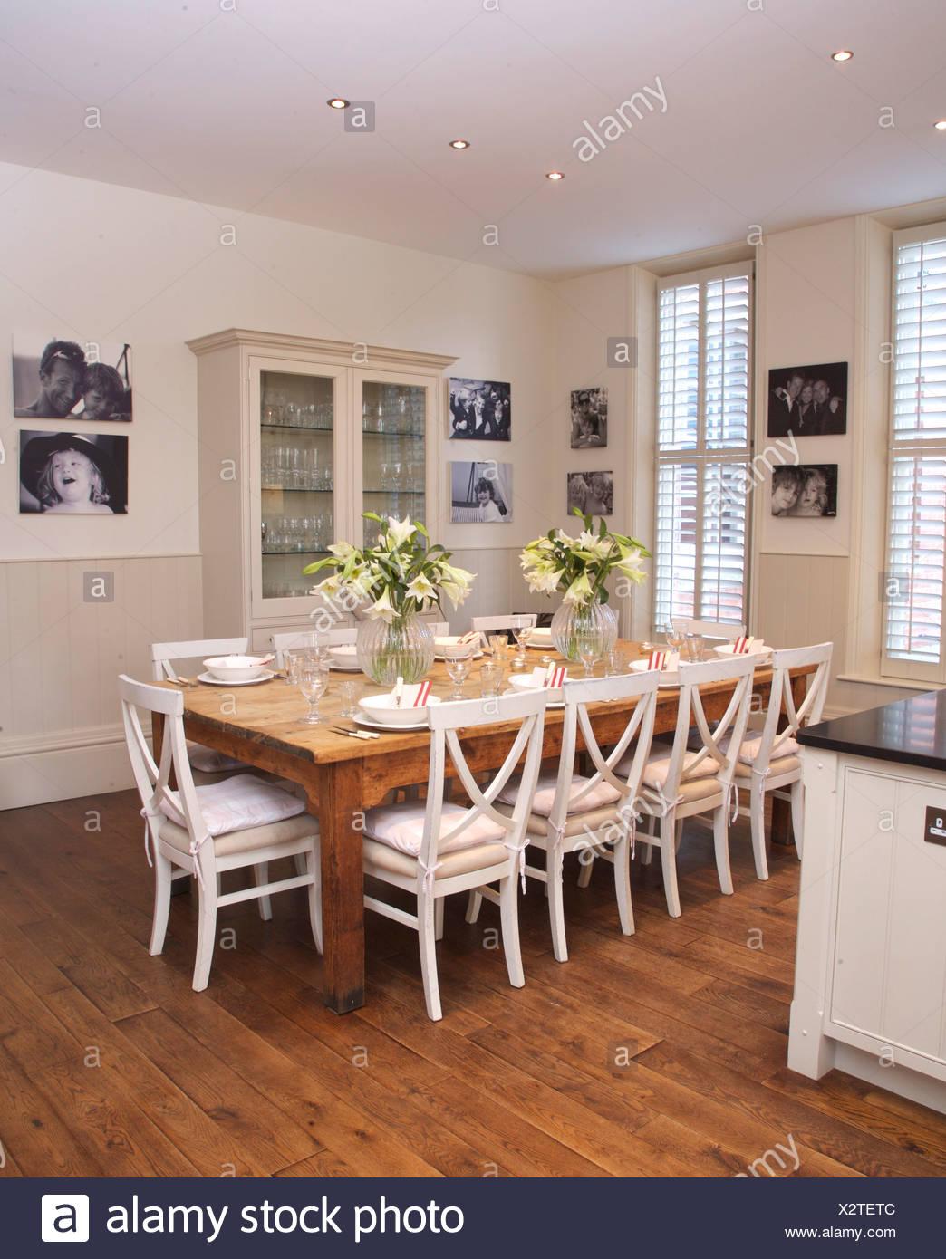 Weiße Stühle Bei Einfachen Holztisch In Moderne Weiße Küche Esszimmer Mit  Parkettboden Und Gerahmten Schwarz + Weiß Fotografien