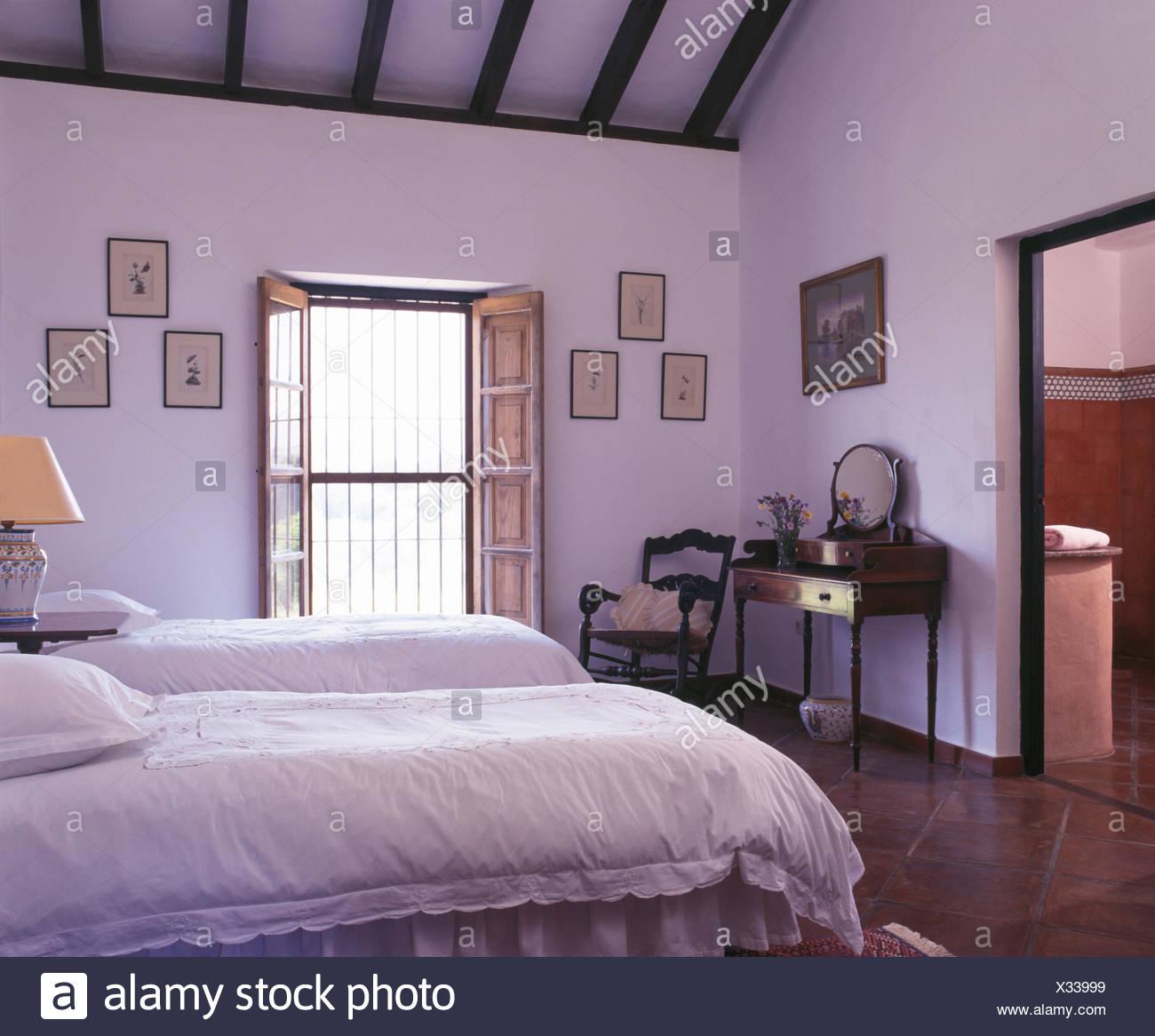 Weiße Bettdecken auf zwei Einzelbetten im Schlafzimmer des weißen ...