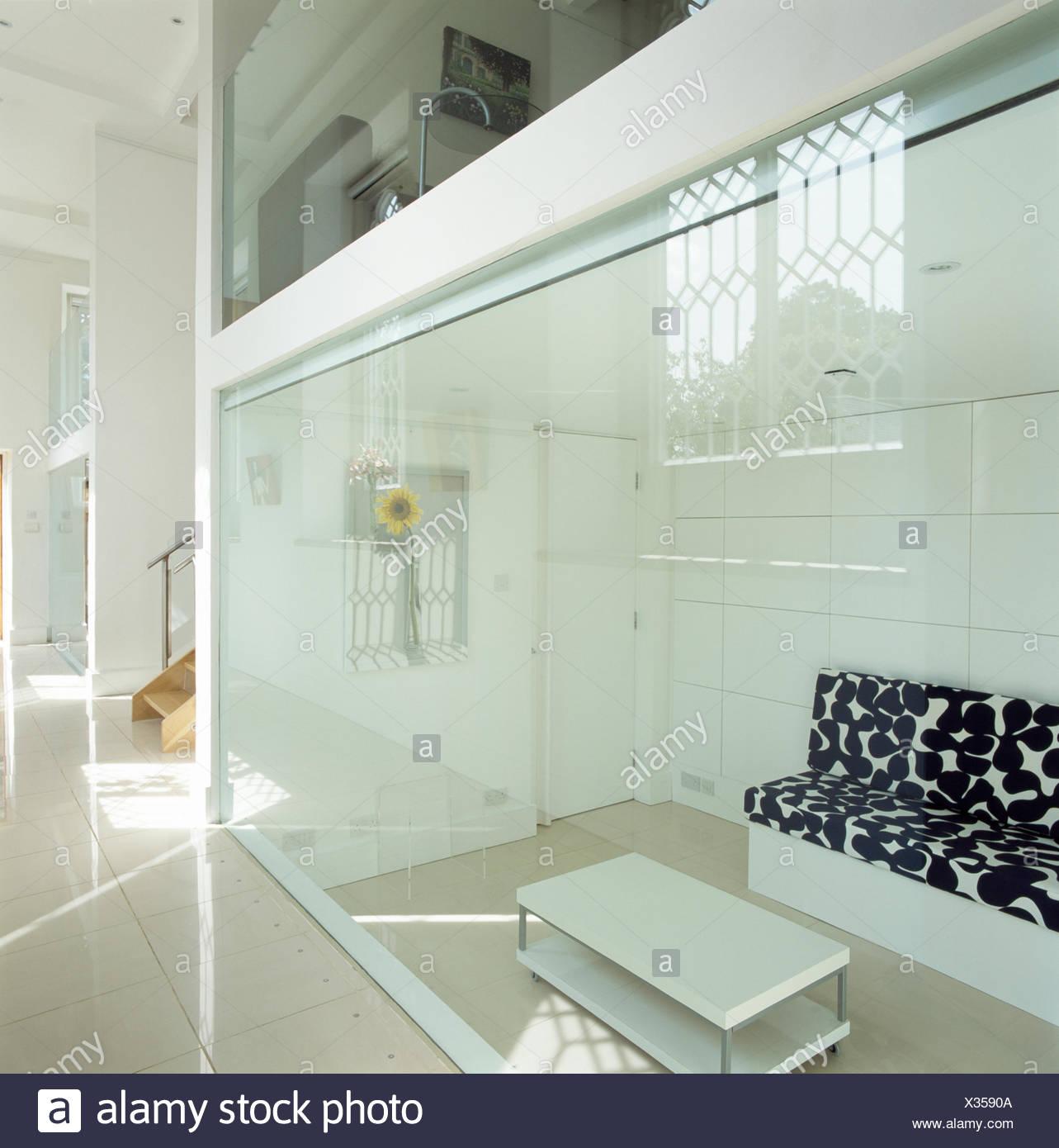 Blick Durch Die Glaswand Des Modernen Wohnzimmer Sofas Mit Schwarz + Weiße  Kissen Und Weißen Couchtisch
