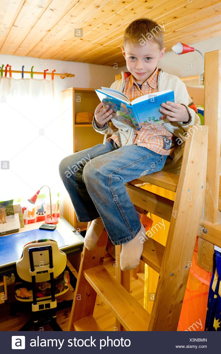 Junge, Sechs Jahre Alt, Sitzt Auf Einem Etagenbett Leiter Während Des  Lesens Einer Bibel Für Kinder