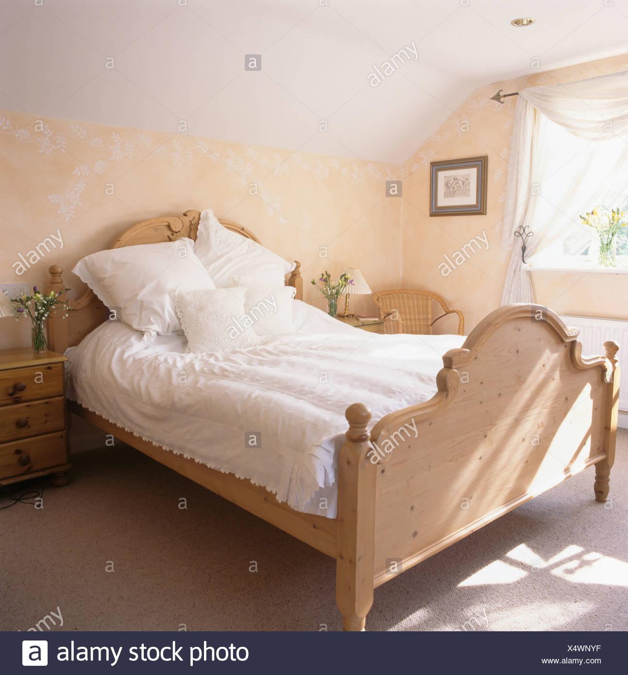 Weiße Bettwäsche auf Kiefer-Bett im Schlafzimmer mit Schablone ...