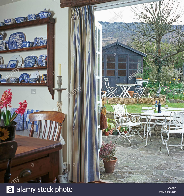 Blick Auf Innenhof Durch Offene Glastüren In Ferienhaus Dining Room Mit  Antiker Tisch Und Regalen Mit Sammlung Von Blau + Weiß Porzellan