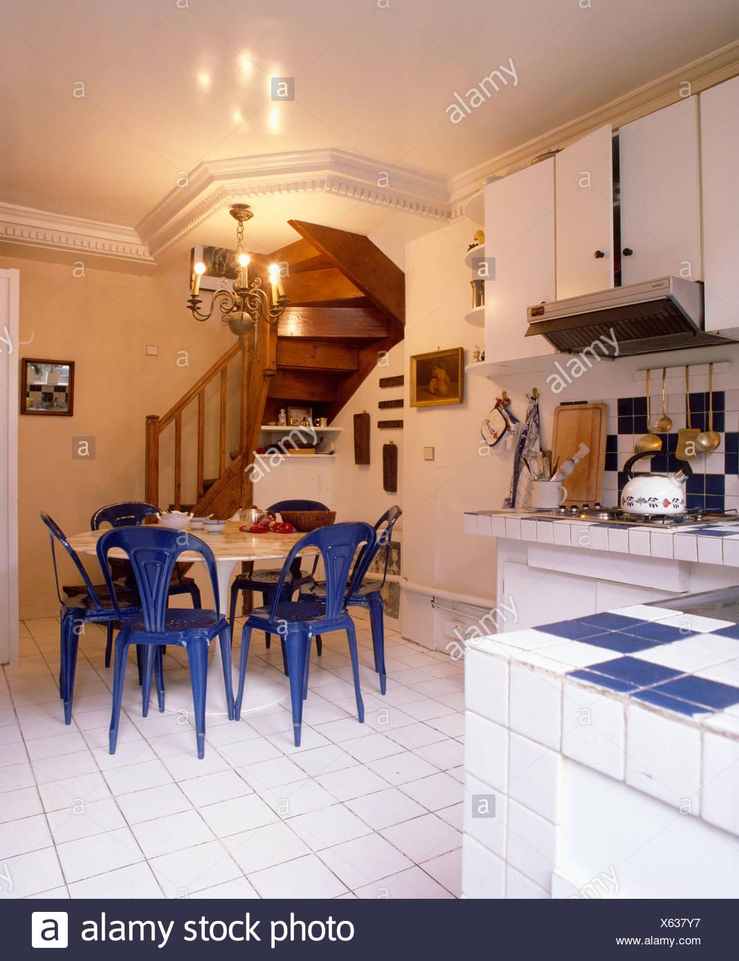 Kronleuchter über Dem Weißen Tisch Mit Blauen Stühlen In Weiße Küche Mit  Weißen Fliesenboden