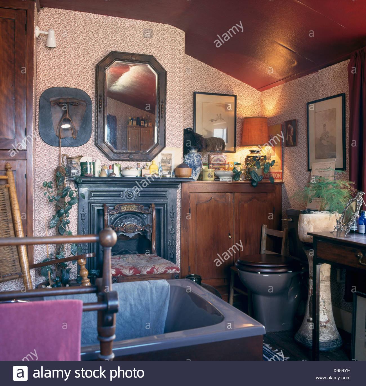 Blaues Bad im kleinen Badezimmer mit Tapeten und beleuchteten Lampe ...