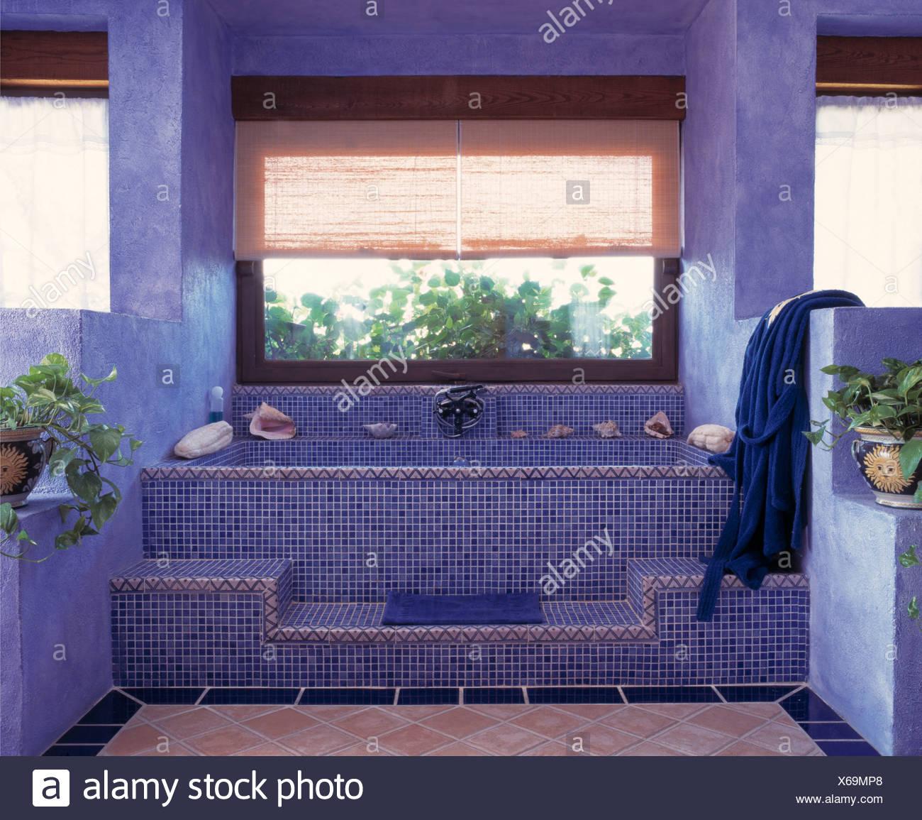split cane blind auf fenster oben hell blauen mosaik gefliest bad im