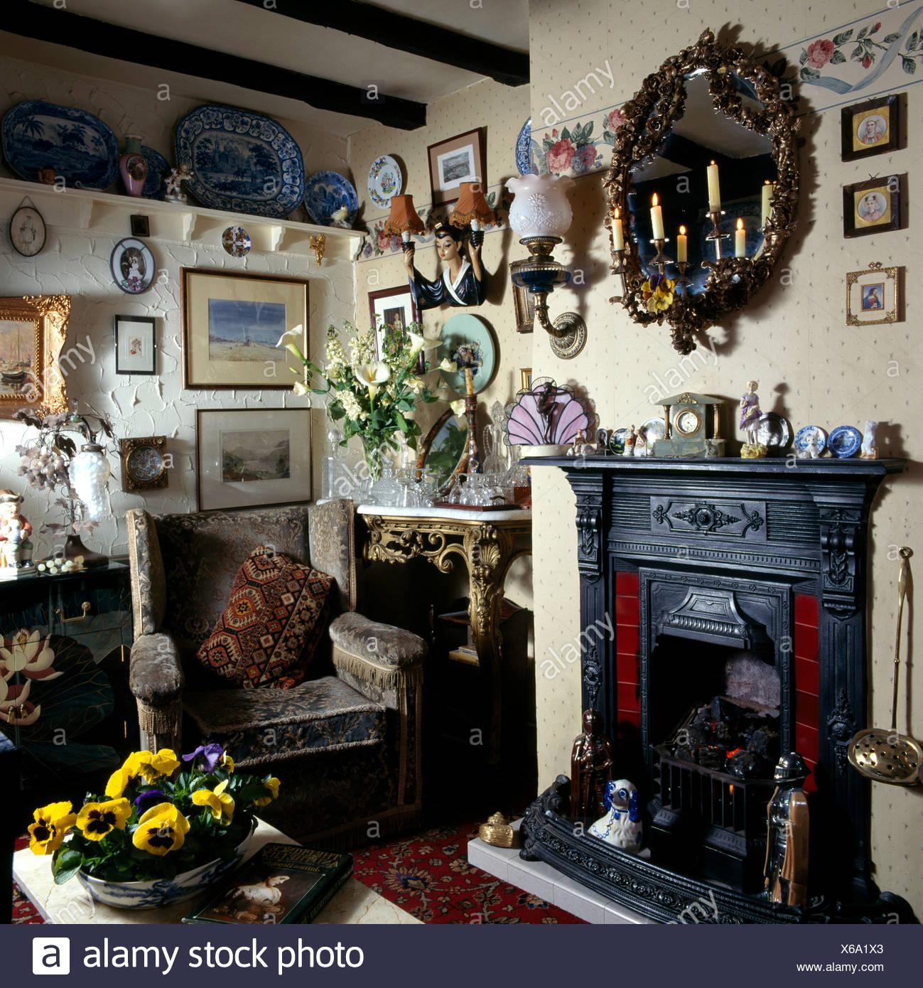 Girandole Spiegel Mit Brennenden Kerzen über Gusseisen Kamin Im Kleinen,  überfüllten Viktorianischen Wohnzimmer Mit Grauen Sessel