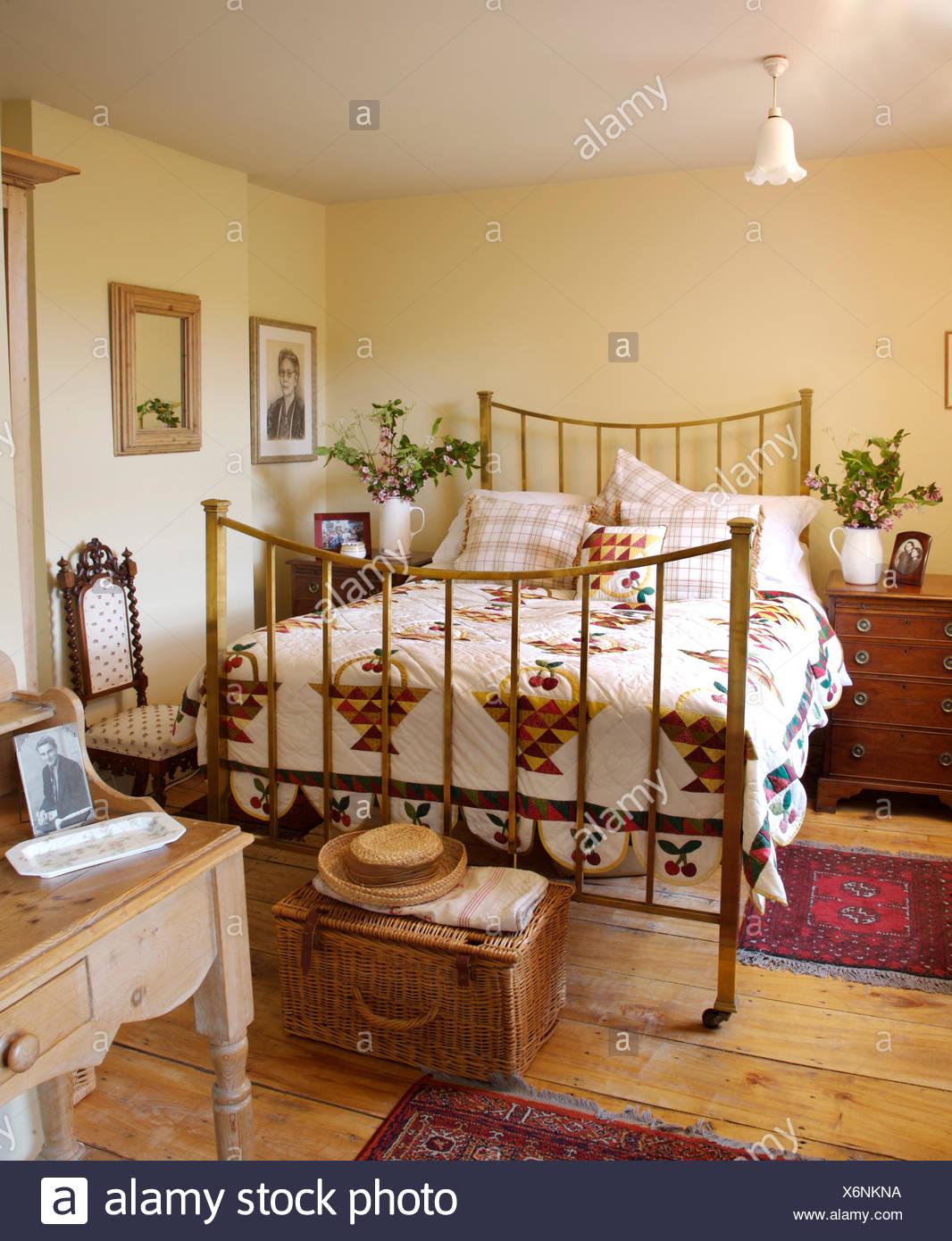 Alte Weide Truhe am Fuße des Messing-Bett mit einem Flickenteppich ...