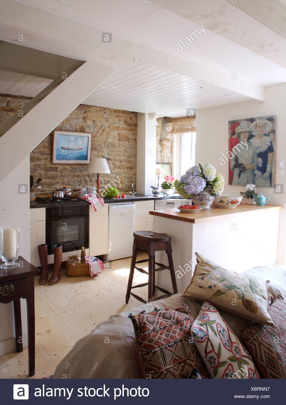 Gemusterte Kissen auf Sofa im Landhaus Küche mit Bild auf Backstein ...