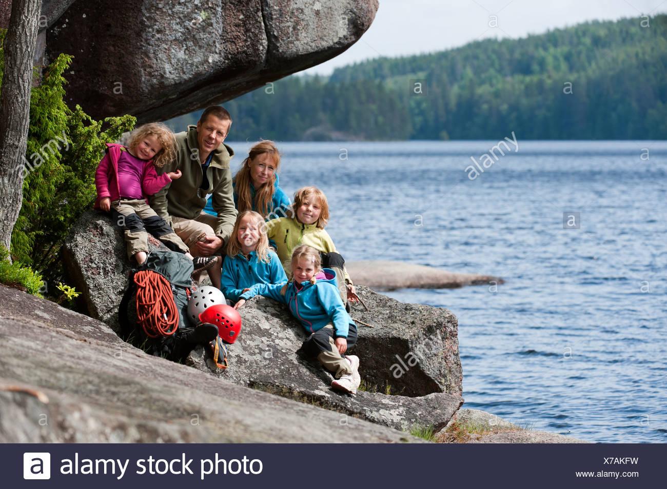 Kletterausrüstung Kinder : Familie mit vier kindern sitzen in der nähe des felsens ihre