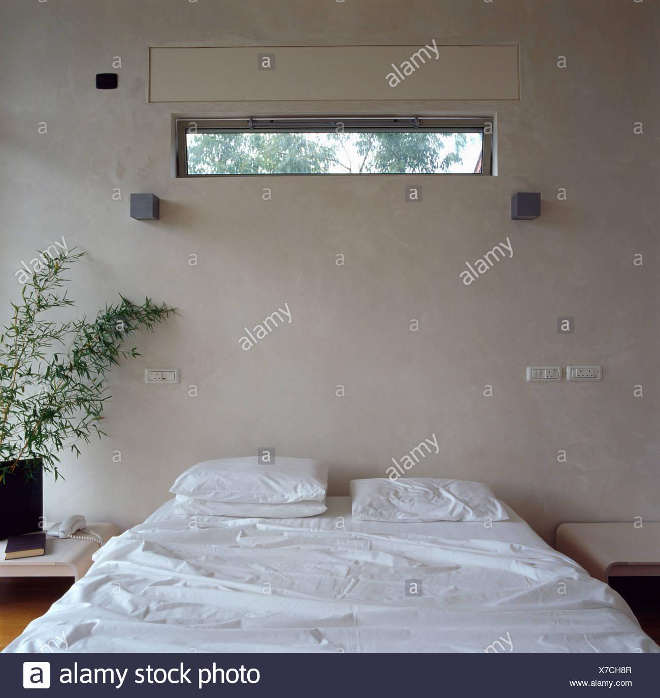 Schmale Fenster über Bett Mit Weißen Bettwäsche In Modernen Weiße  Schlafzimmer