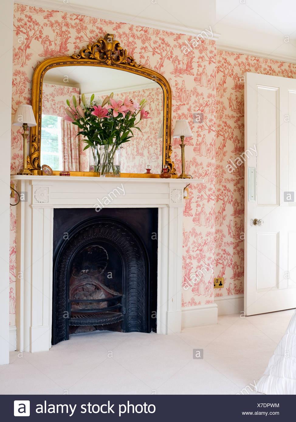 Große vergoldete Spiegel über dem Kamin im Schlafzimmer mit rosa ...