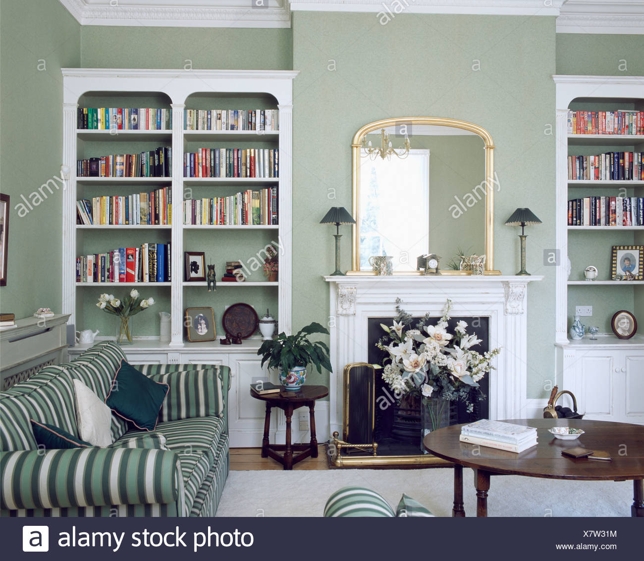 Weiße Regale Auf Beiden Seiten Der Kamin Im Wohnzimmer Grau Grün Mit Grün +  Weiß Gestreiften Sofa Und Antiker Tisch Ausgestattet
