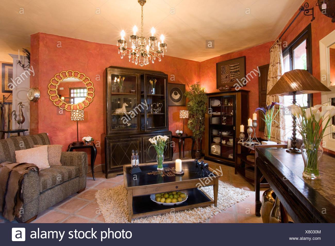 Dunkelbraune Möbel Und Moderne Kronleuchter Im Spanischen Wohnzimmer Mit  Orange Wand