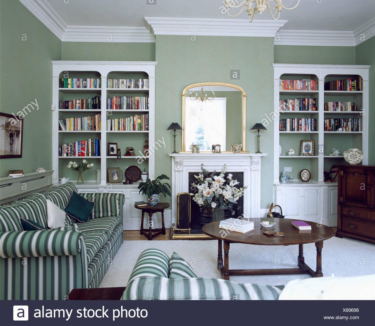 Weiße Regale Auf Beiden Seiten Der Kamin Im Wohnzimmer Grau Grün Mit Grün  Gestreiften Sofas Und Antiken Couchtisch Ausgestattet