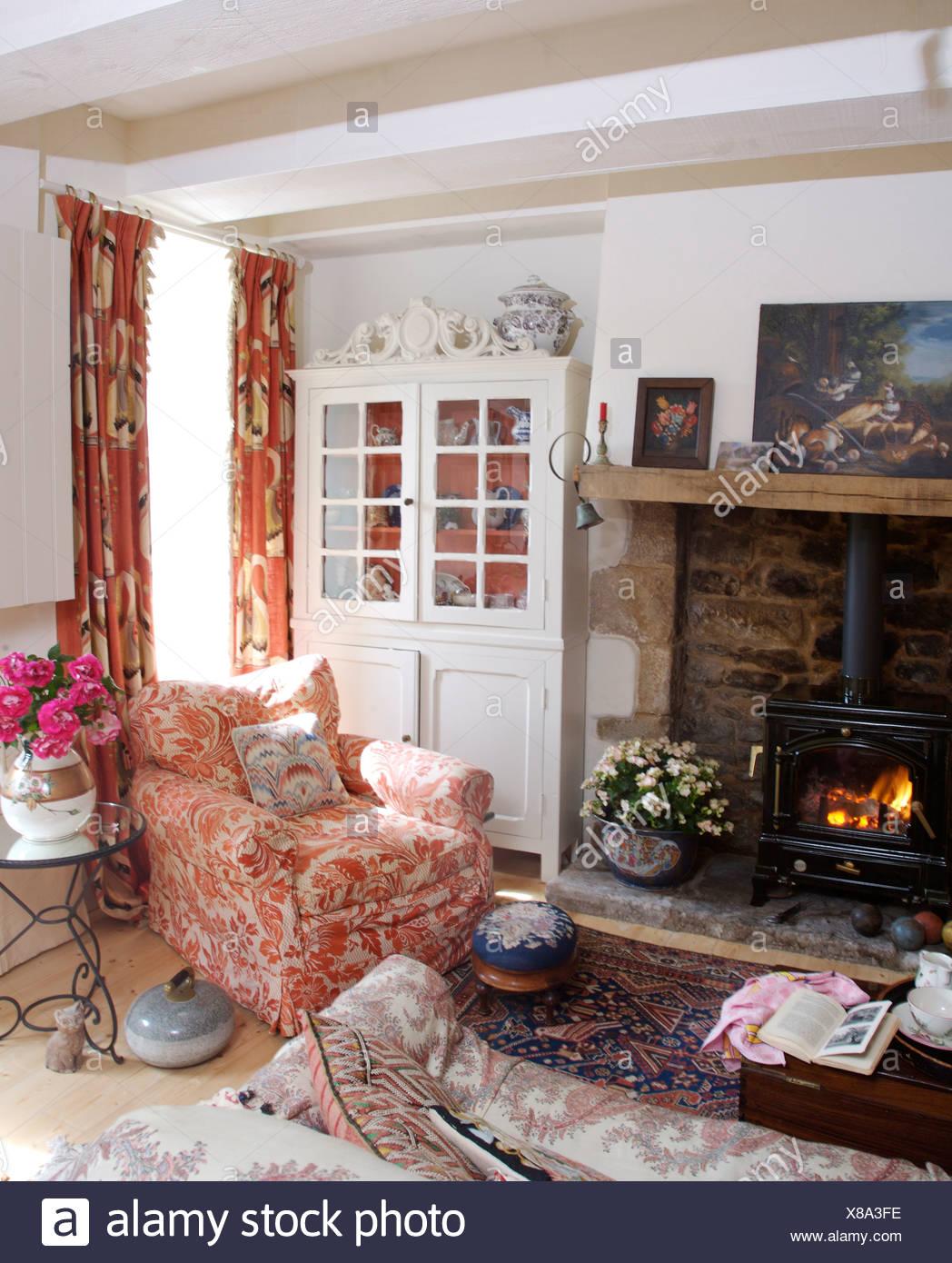 Rosa + weiße Sessel am Kamin mit Holzverbrennung Herd in ...
