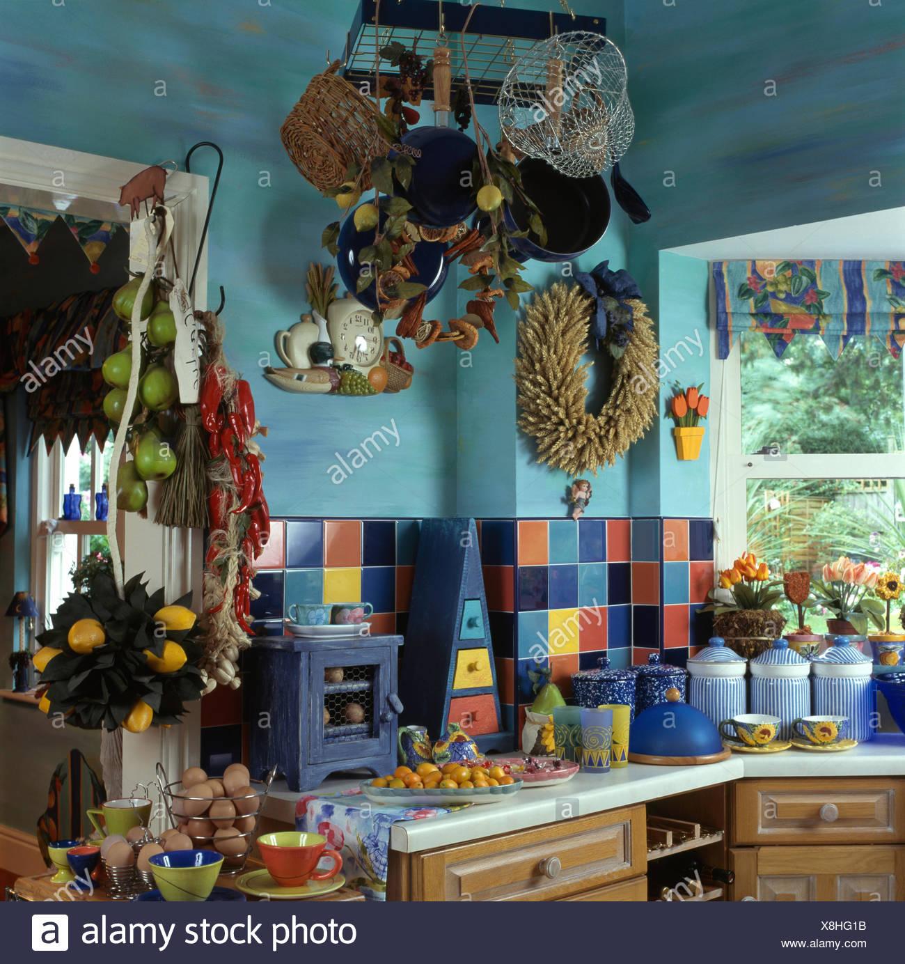 Bunte Kacheln Auf Splash Zurück In Einer Kleinen Blauen überladen Der  Neunziger Jahre Küche Mit Körben Und Töpfen Auf Hängenden Rack