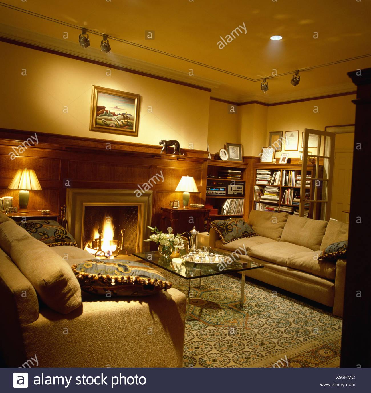 Gemütliches Wohnzimmer Mit Brennenden Lampen Und Beigefarbenen Sofas Am  Kamin