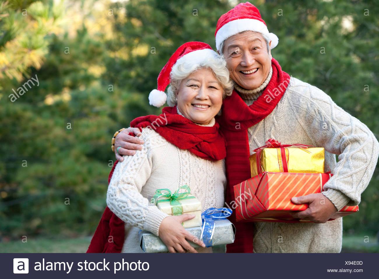 Älteres Paar in Santa Hüte halten Weihnachtsgeschenke Stockfoto ...