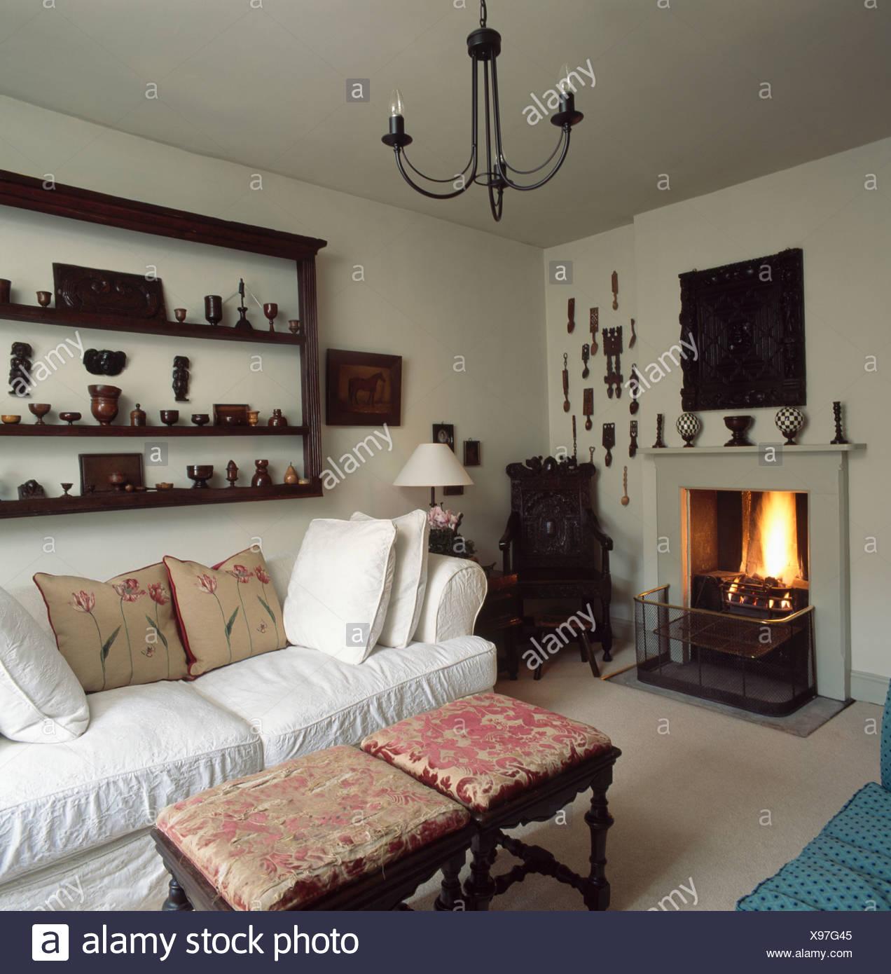 Sammlung Von Treen Auf Antiken Regalen über Weißen Sofa Im Wohnzimmer Land  Mit Brennenden Feuer Im Kamin