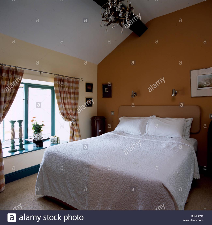 Schlafzimmer im Dachgeschoss mit weißer Decke auf dem Bett Stockfoto ...
