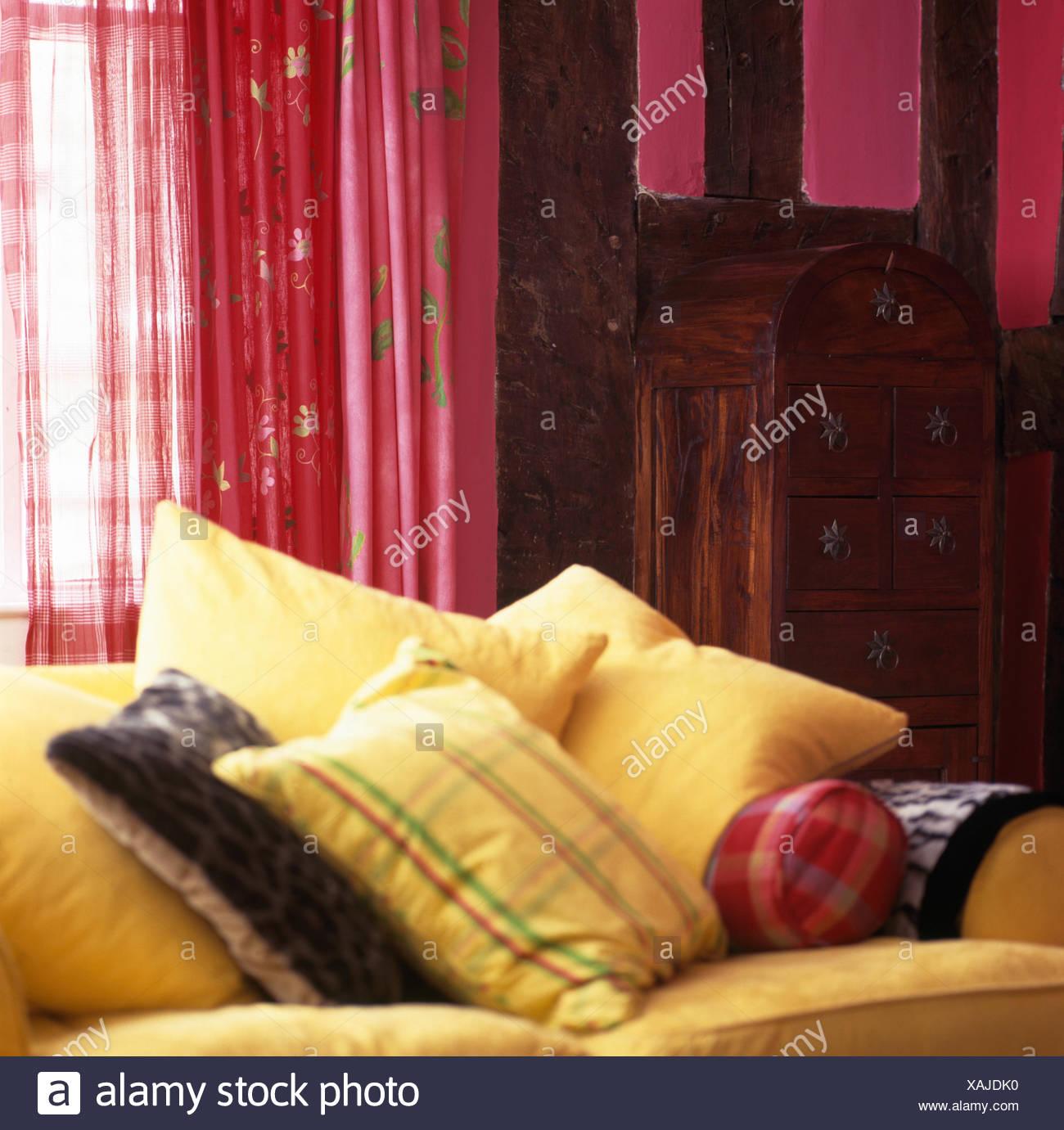 Gelbes Kissen Auf Gelben Sofa Vor Fenster Mit Rosa Vorhängen In Einer  Neunziger Jahre Wohnzimmer Mit Rustikaler Holzschrank