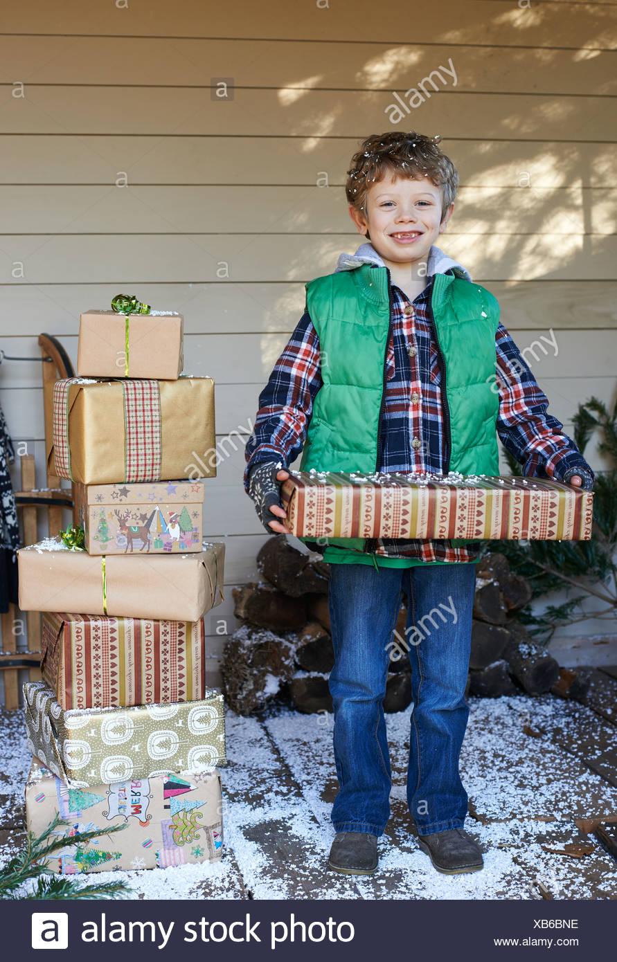 Junge hält Weihnachtsgeschenke auf verschneiten Veranda Stockfoto ...