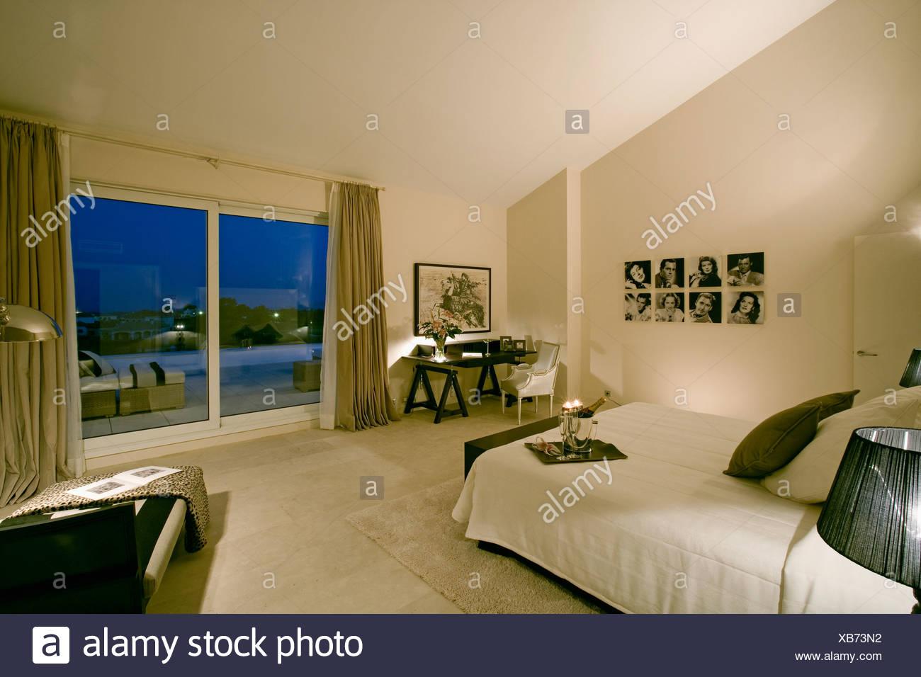 Moderne Neutralen Spanischen Schlafzimmer Mit Blick Durch Glas  Terrassentüren Der Pool Bei Nacht