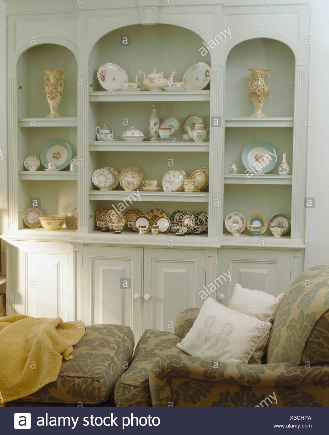 Sammlung Von Antiken China Auf Alkoven Regale In Hellgrau Mit Gemusterten  Sessel Kommode In Pastell Grün Wohnzimmer Ausgestattet