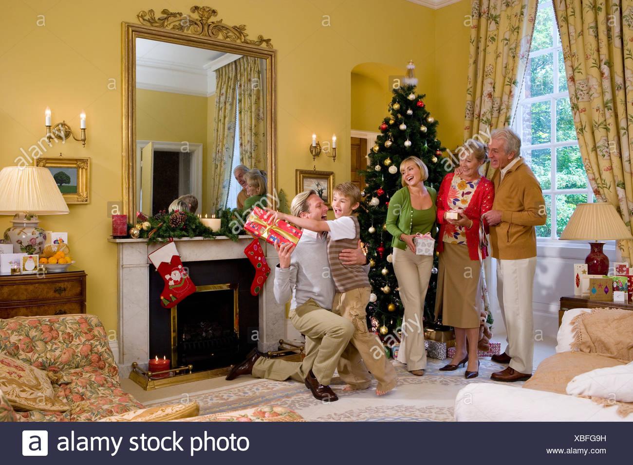 Familie mit präsentiert von Weihnachtsbaum, junge (9-11) Griff nach ...