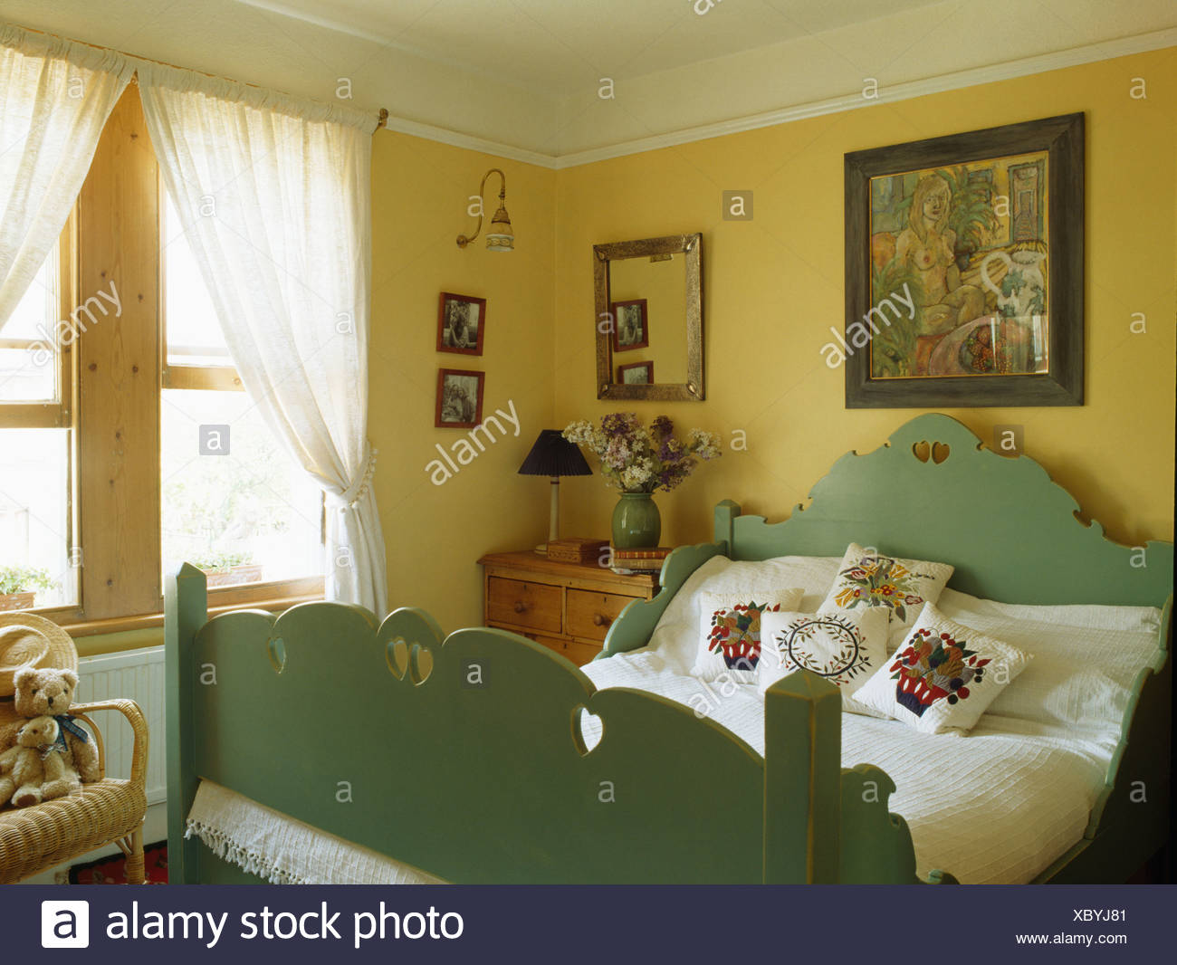Bild An Der Wand Oben Grün Lackierten Holzbett Mit Bestickten Kissen Im  Gelben Schlafzimmer Mit Weißen Voile Vorhänge Am Fenster