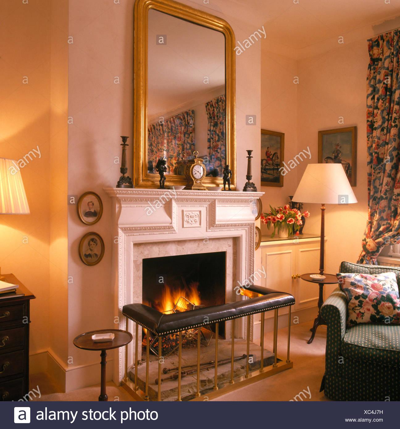 Vergoldeter Spiegel über Kamin Mit Club Kotflügel Im Gemütlichen Wohnzimmer  Mit Brennenden Lampen