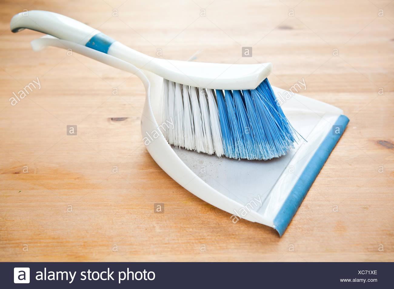 Holzfußboden Reinigungsmittel ~ Ein kunststoff schaufel und el auf einem holzfußboden