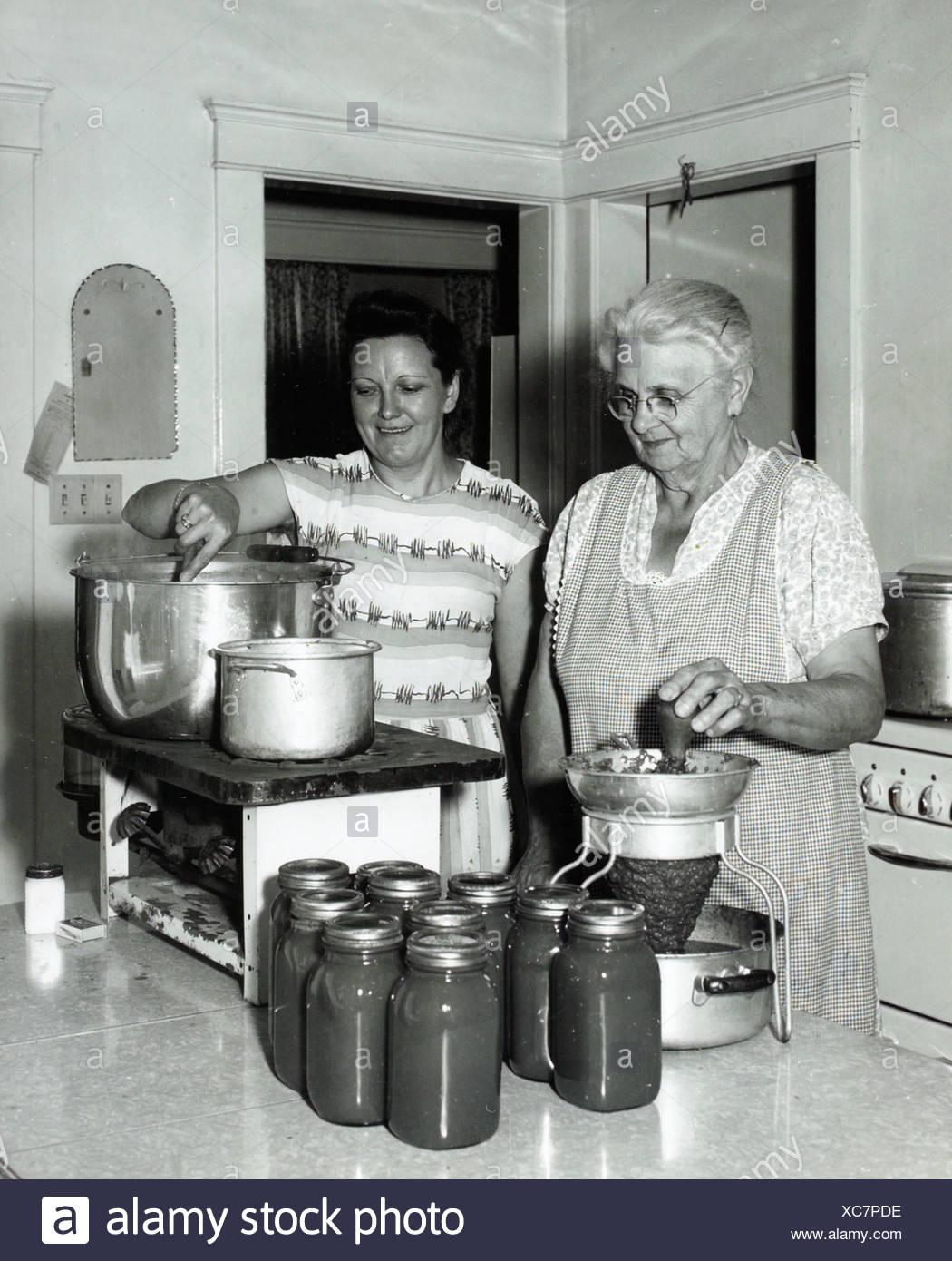 Zwei Frauen, die Konservierung von Gemüse in der Küche 1950 s ...