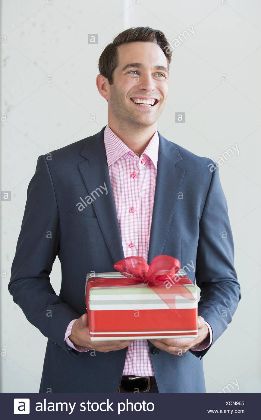 Gut gekleideter Mann mit Weihnachtsgeschenk Stockfoto, Bild ...