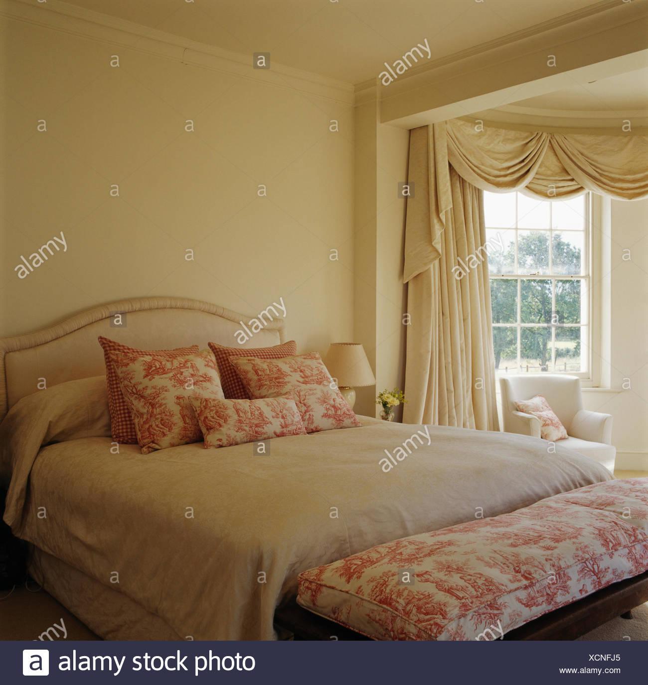 Rosa Toile-de-Jouy-Hocker und passende Kissen auf dem Bett mit ...