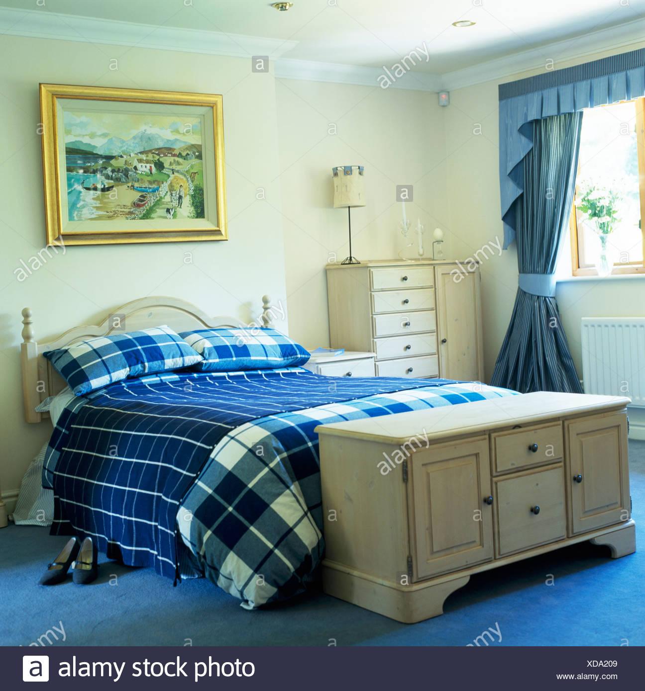 Blasse Holz Brust Unter Bett Mit Blauen Aufgegebenes Bettdecke Und Wurf In Creme  Schlafzimmer Mit Tief Blauen Teppich Und Vorhänge