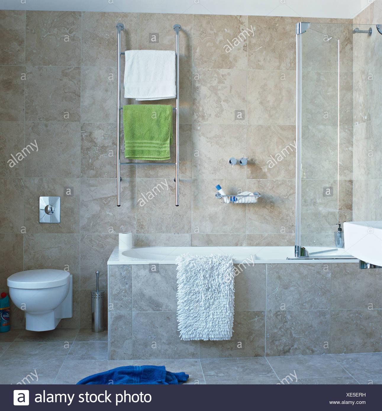 Handtücher auf beheizten Chrom Schiene auf Wand über Bad mit Glas ...