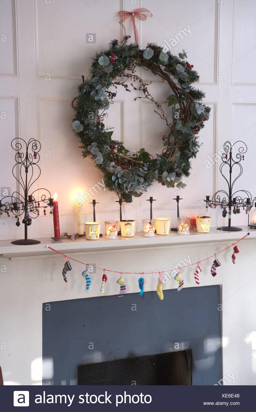 Fesselnd Efeu Und Koniferen Kranz über Dem Kamin Dekoriert Für Weihnachten Mit  Brennenden Kerzen Auf Kaminsims Und Girlande Aus Winzigen Strümpfe
