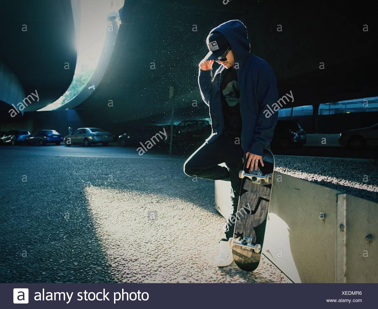Junger Mann Stehen Auf Einem Bein Mit Skateboard Unter Brücke