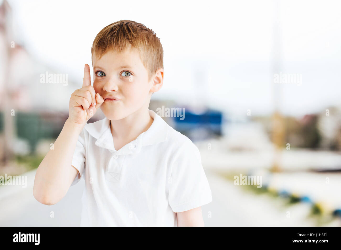 little boy show emotions at park background with light stock photo