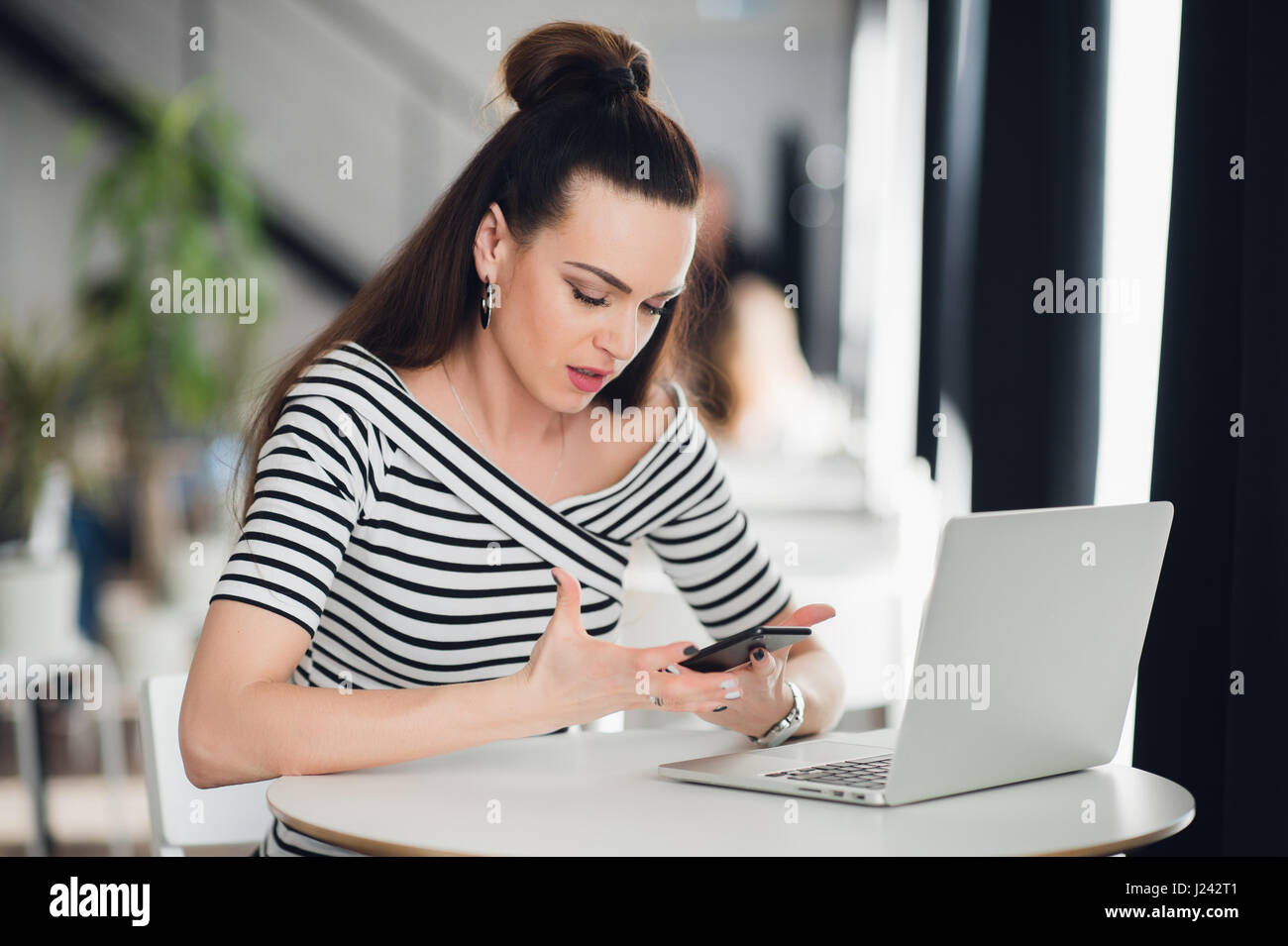 Frustrated office worker on the phone holding stock photo image - Disappointed Businesswoman Looking At Business Results On Phone Screen In A Cafe During Lunch Break